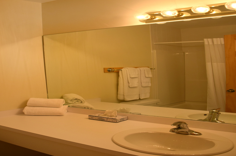 Bathroom with tub, large counter, and hairdryer