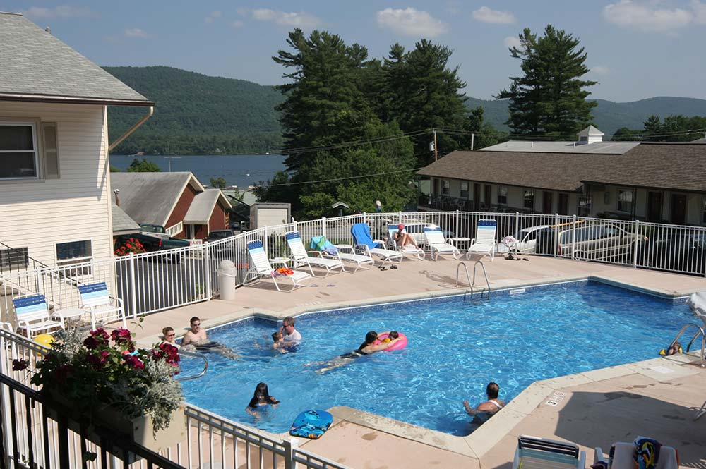 Guest swimming in pool overlooking lake